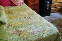 King size single bed with comfy quilts.