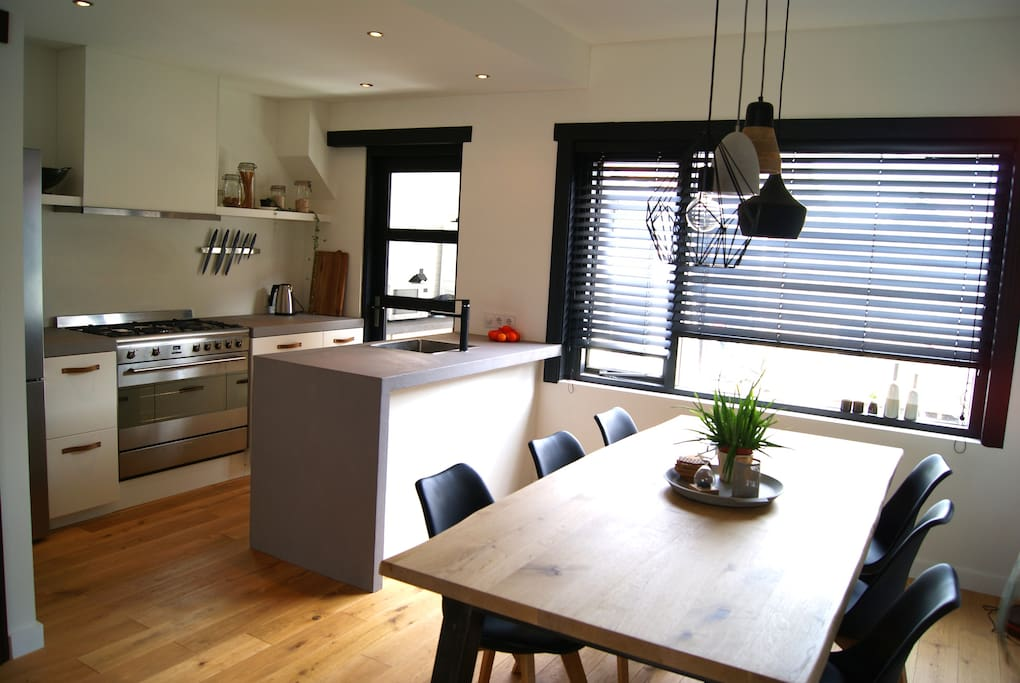 Open concrete-countertop kitchen, equiped with new modern appliances. Including 5-burner stove, large oven and dishwasher