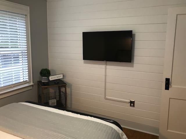 """Bedroom 1: 43"""" smart TV, handcrafted bourbon barrel side table."""