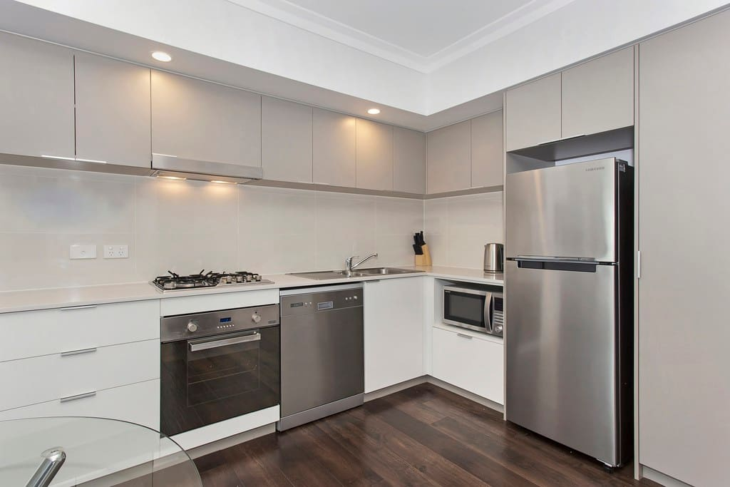 Fully furnished kitchen with dishwasher, oven, gas stove, fridge, microwave