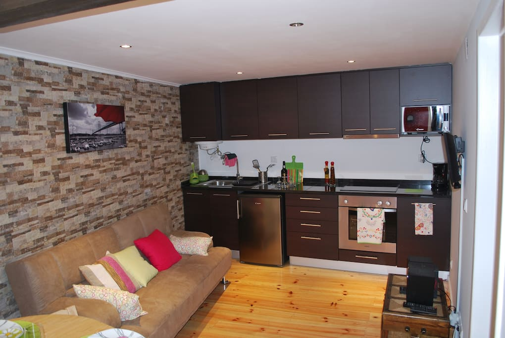 A nice living room with a fully equipped kitchen. Simple and practical.