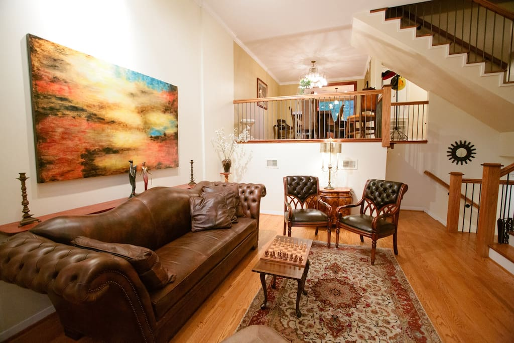 Warm and bright living room with fireplace, large flatscreen TV and sliding glass doors to patio.