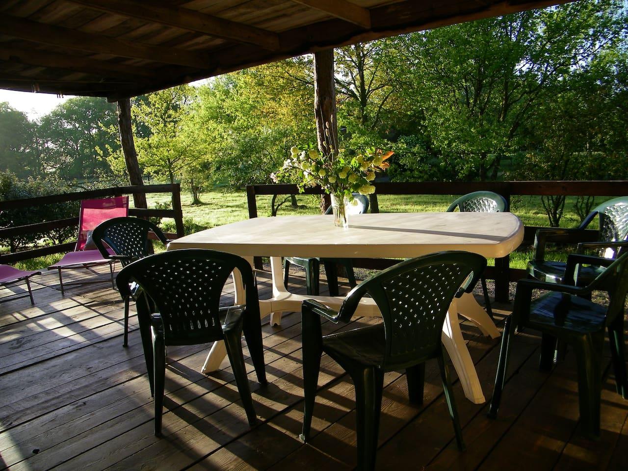 Votre terrasse privative couverte où vous pourrez prendre vos repas et vous détendre. Vous profiterez d'une vue agréable sur le parc arboré.