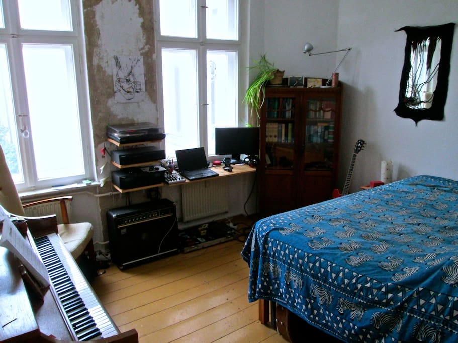 The cosy Bed and Living room with a piano, guitars,sound system and old record player.
