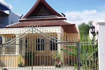 Front view of villa with stainless steel remote controlled entrance gate. Parking for 3 cars and motorbikes. Table and 6 chairs just in case it rains.