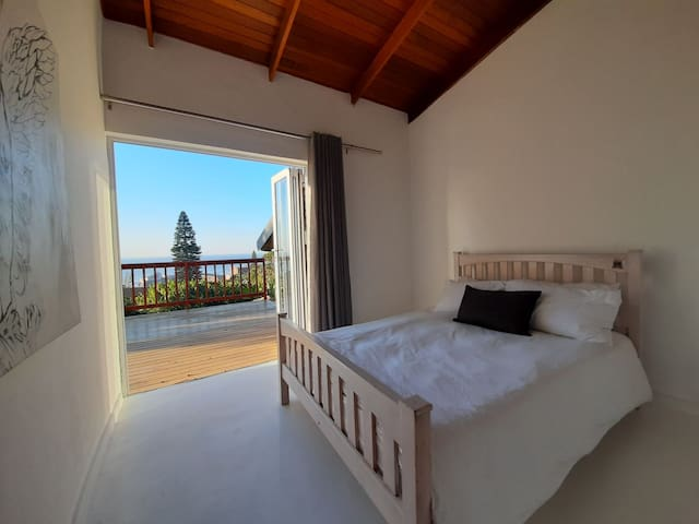 Bedroom with full sea view with fold back doors leading onto the deck area and down to the pool.
