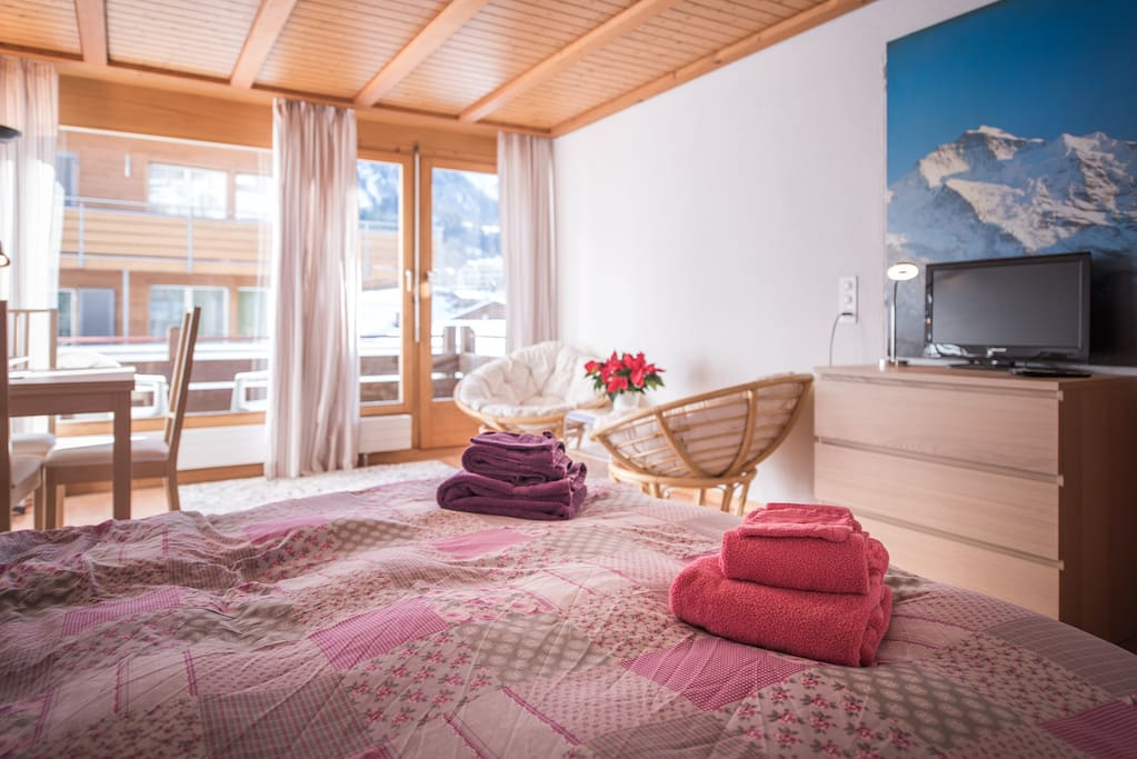 Open plan living area, with double bed, seating, coffee table and a view of the Jungfrau!