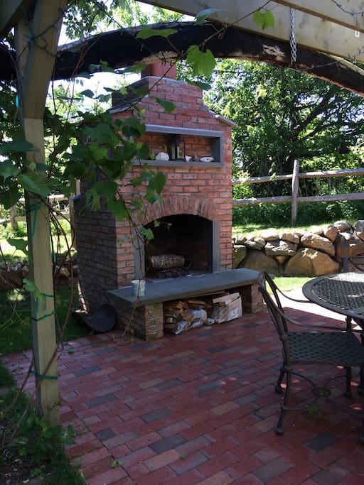 outdoor dining room with fireplace under grapevine trellis