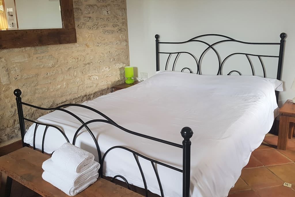 King sized bed with memory foam mattress, beautiful stone wall, and pure cotton white linen