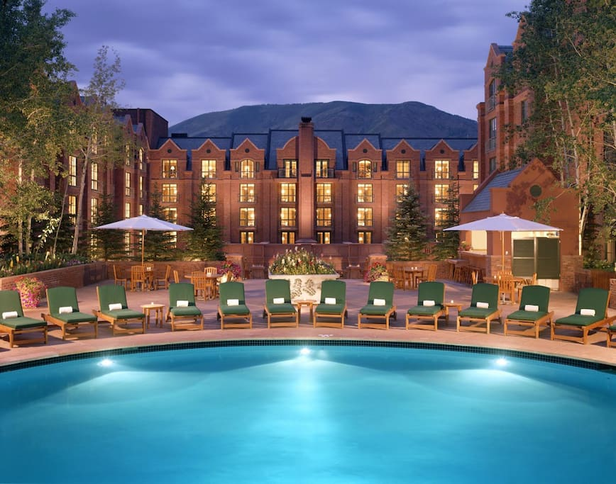 The expansive courtyard features a large outdoor pool in the center, flanked by three hot tubs.
