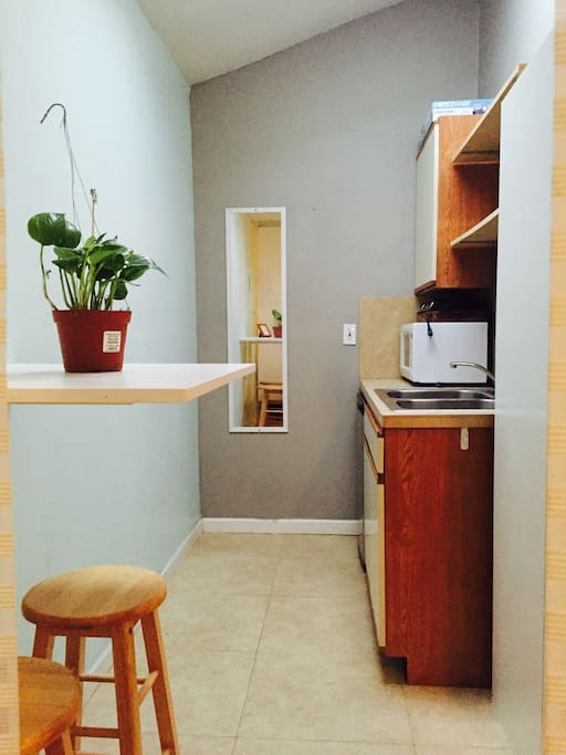 Kitchenette area with sink, microwave, and cabinet storage for non-perishable  goods.  Mini refrigerator located beneath microwave.