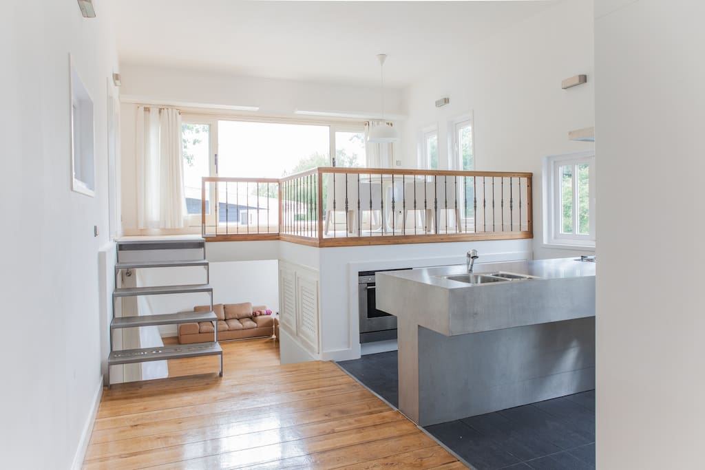 you look from the kitchen into the living room (downstairs) and upstairs the dining area with terras