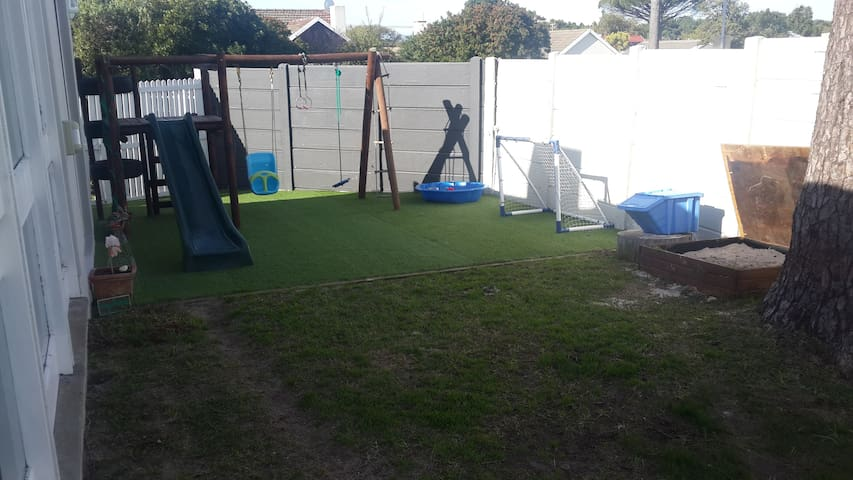 outdoor play area with jungle gym, sandpit and Astroturf