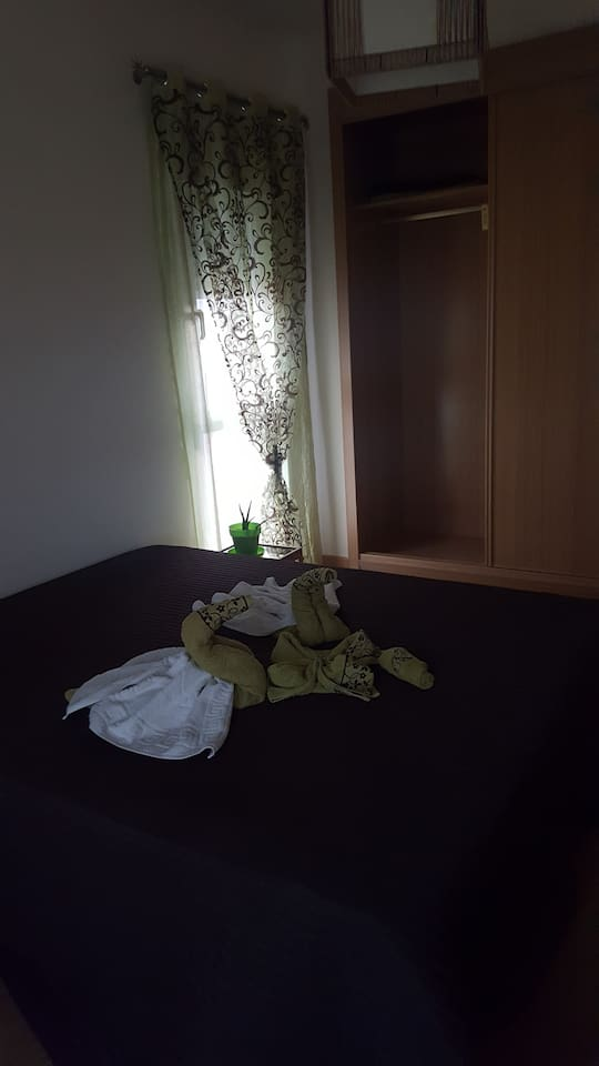 Habitacion con armario, cama de 1m50 y tiene 2 ventanas dan al patio trasero de la casa