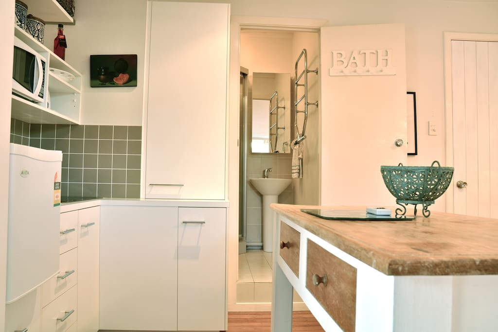 Kitchen area with bathroom in background