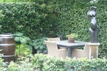 Zitje in de achtertuin, met beeld (kunst), bij mooi weer kunt u hier heerlijk ontbijten