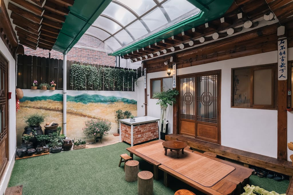 Inner yard with flat wooden bench and table is kind of living room where everybody can come together to talk and have a party