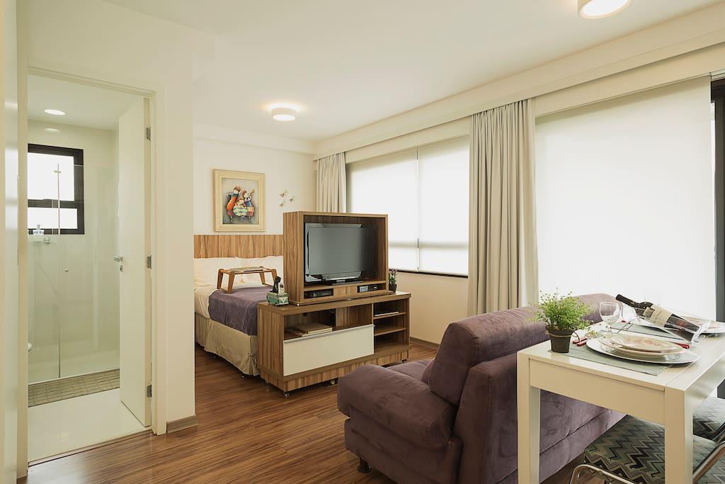 cama de casal com tevê giratória, onde o hóspede pode assistir no sofá ou na cama