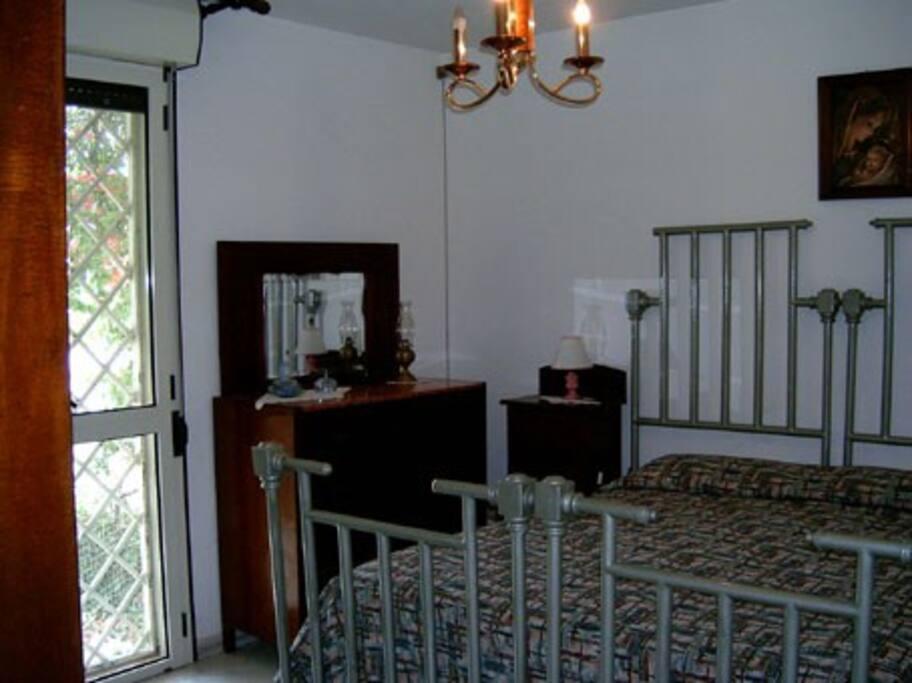 Camera da letto matrimoniale e accesso al giardino posteriore