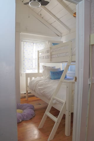 View of entrance into bunk bed room, with full-sized bed at bottom and twin-sized bed on top. Vaulted ceilings with overhead, adjustable fan and dimmer light.