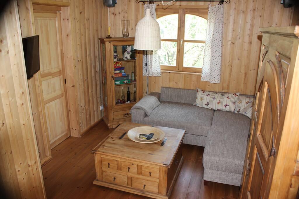 Wohnzimmer mit Schlafcouch und Schlafzimmertür