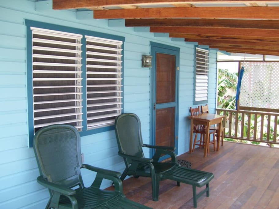 Front porch with chairs, table and hammocks