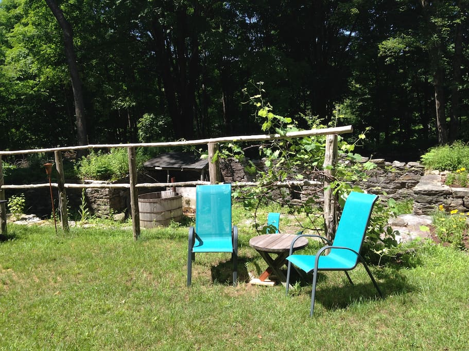 The side yard with small seating area, and grill and picnic table for outdoor dining (not pictured).