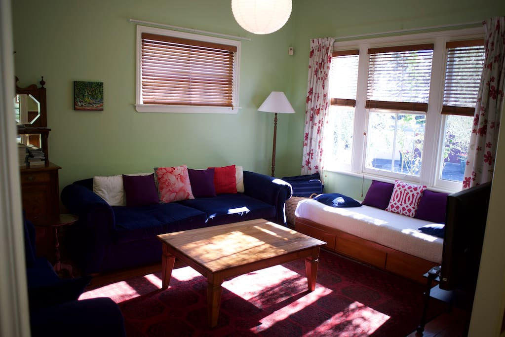 Large lounge with comfy sofa's and coffee table. Flat screen TV, Venetian blinds, heat pump (offscreen), lights.