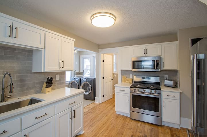 This beautifully remodeled kitchen sports brand new stainless appliances and quartz countertops