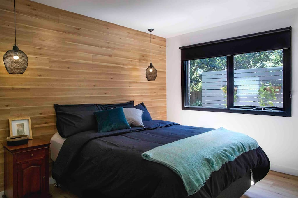 The second of our beautiful guest bedrooms, featuring stunning timber wall, pendant lighting, Queen bed with sumptuous mattress topper, professionally laundered linen and cosy duvets. Block out blinds are provided for privacy and allow a sleep in.