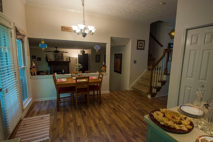 This photo gives a view of the breakfast nook, living room and stairs that lead to the 2nd story.