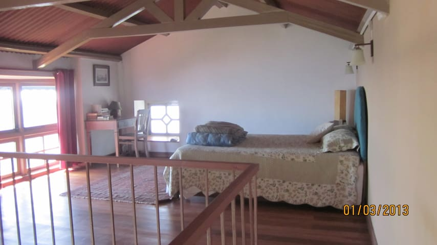 The loft bedroom is spacious, with a writing desk in the corner. Panoramic view of the valley and mountains from the large window
