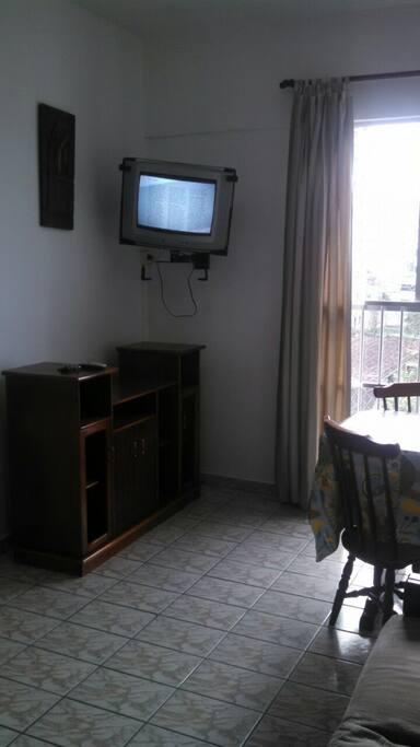sala com mesa de jantar, tv e sofá