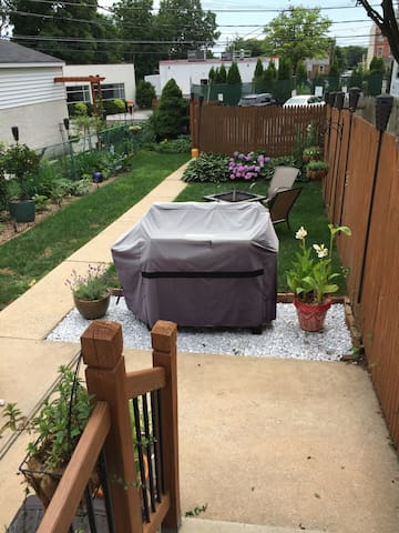 Backyard with fire pit, propane and charcoal grill, seating for 4-6, and 3 off street parking spots.