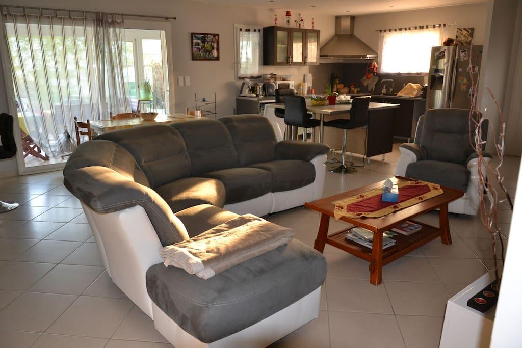 Bel espace de salon avec cuisine et îlot central.