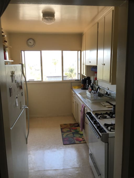 Nice kitchen with microwave, gas stove, huge refrigeration, gorgeous Hollywood Hills window views!