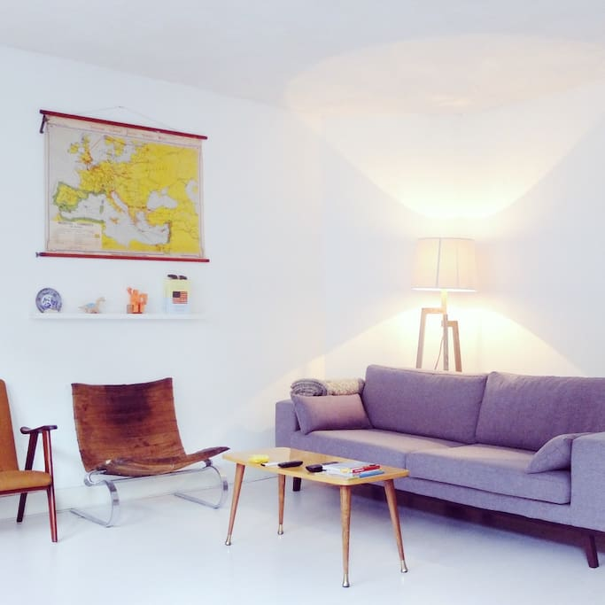 The living room with a old map on the wall and a design lamp in the back.