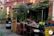 Banquette et table intimiste entourées par les plantes du potager, pour un voyage au calme et hors cadre plein cœur du vieux Lille