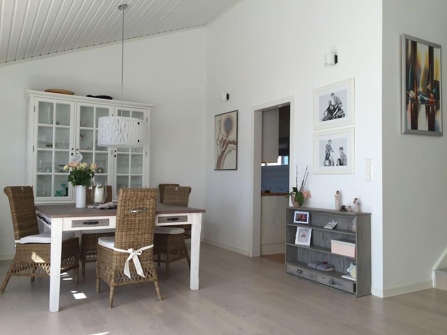 Stue med vinduer mot utsikt og uteplass. Spisestue
