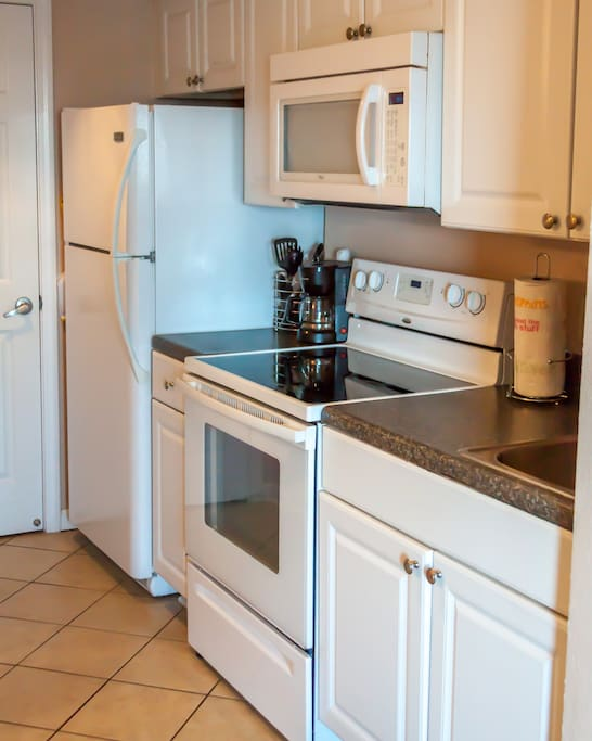 Fully equipped kitchen. Cookware, utensils, coffee maker, toaster, blender, spice rack,  and dishes.
