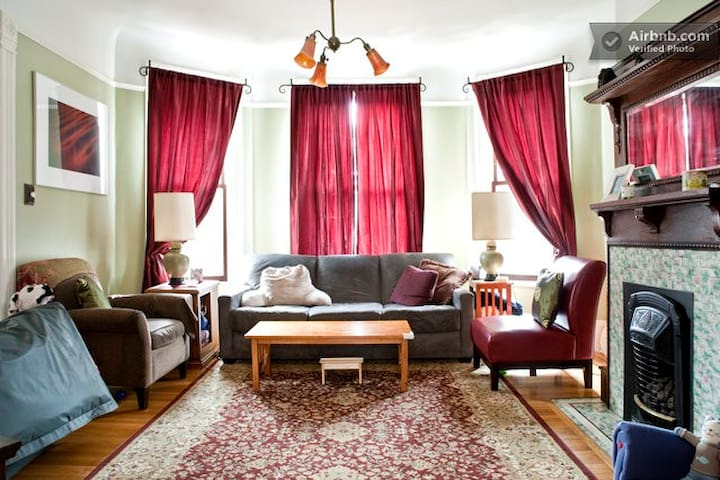 (Shared) living room with bay windows, gas fireplace, tv.