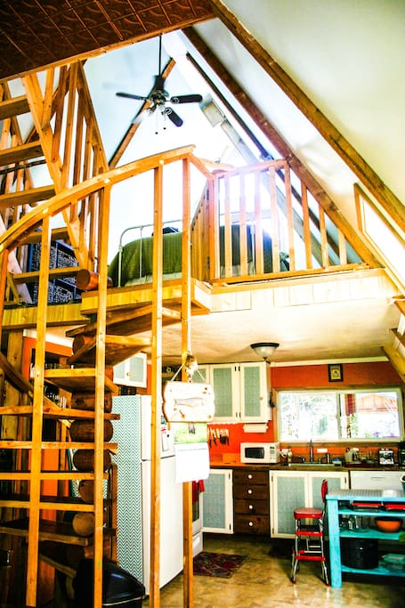A frame cottage features kitchen downstairs, sleeping loft upstairs, and reading nook in the third floor crow's nest.