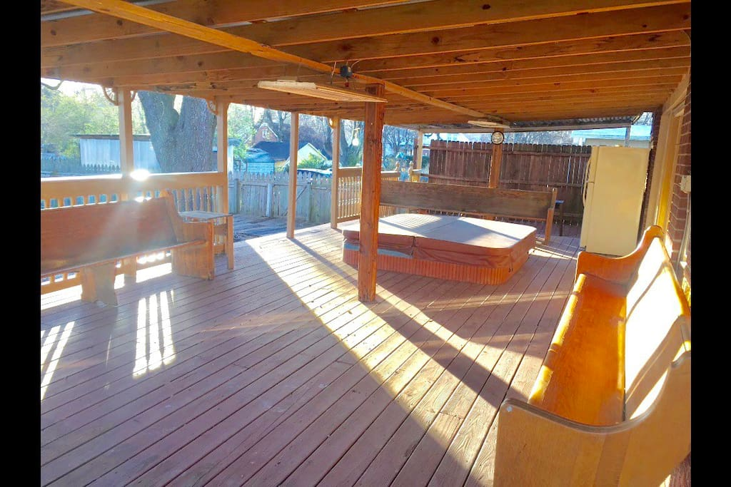 Large deck with jacuzzi hot tub and church pews