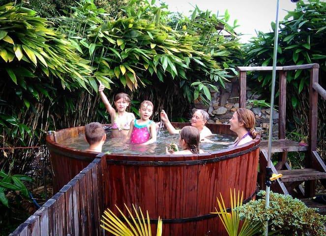 Familia disfrutando de un baño en tina de madera con aguas calientes.