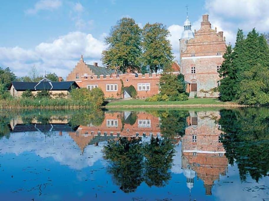 Broholm Slot set fra sydsiden med søen og museet i forgrunden