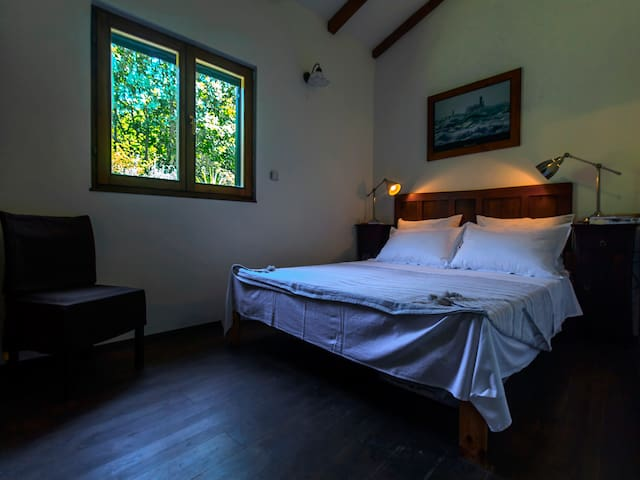 bedroom 1. with high ceiling which is decorated with sloping wooden beams