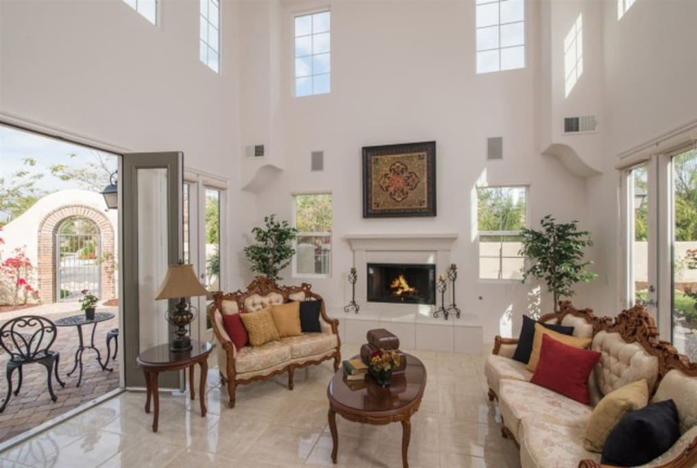 To the left a 2-story Living Room with an elegant fireplace and French doors that lead out to both the front and side courtyards. There is abundant light through the home due to the 12  French doors throughout - many come with Hunter Douglas blinds