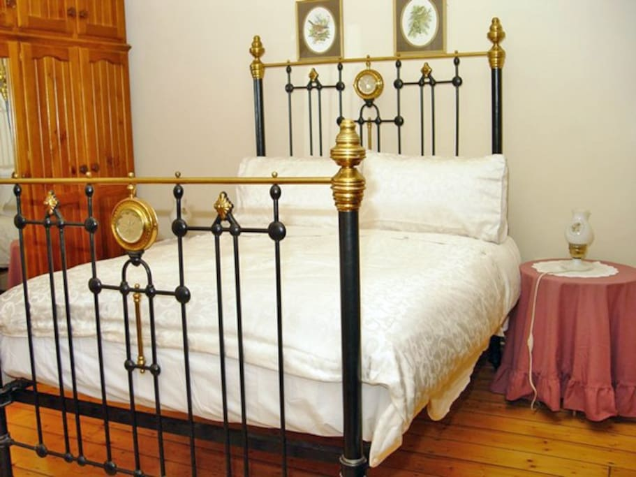 Large bedroom with antique double brass bed