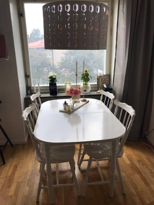 Mysigt bord i vardagsrum. Det finns även ett stort bord/avlastningsbord i köket