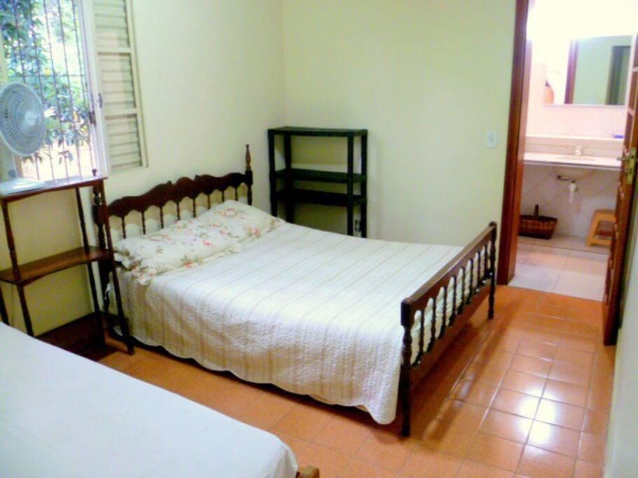 Suíte Lateral: Cama de casal, cama solteiro prateleiras e ventilador.
